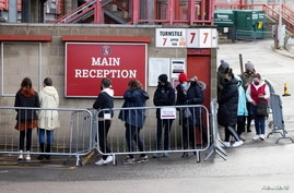 People queue for COVID-19 testing at a mass screening center at Charlton Athletic Football Club, London.