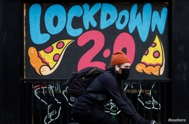 A man cycles past a mural on the boarded up window of a closed pizza restaurant amid the outbreak of the coronavirus disease …
