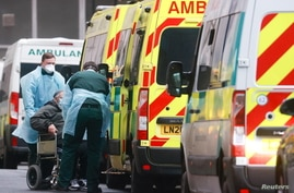 Medics help a patient out of an ambulance at the Royal London Hospital, amid the coronavirus disease (COVID-19) outbreak, in…