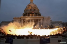 An explosion caused by a police munition is seen while supporters of U.S. President Donald Trump gather in front of the U.S…