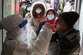 A medical worker in protective suit collects a swab from a resident during a mass nucleic acid testing following a recent…