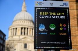 A public health information sign is seen with St. Paul's Cathedral seen behind amidst a lockdown during the spread of the…