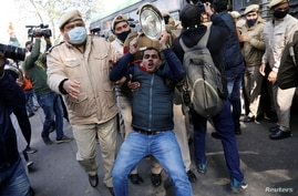 Police officers detain an activist of the youth wing of India's main opposition Congress party during a protest.