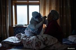 A medical worker in protective suit collects a swab from a bedridden elderly at a house during the second round of citywide…