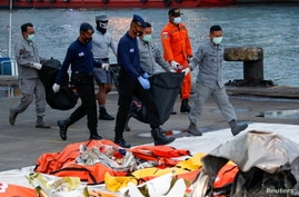 Indonesian DVI and navy personnel carry bags with body parts of the passengers of Sriwijaya Air flight SJ-182, which crashed to the sea, at Tanjung Priok port in Jakarta, Indonesia, Jan. 13, 2021.