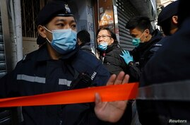 FILE - Daniel Wong Kwok-tung, a lawyer who tried to help the 12 people detained in mainland China, is escorted by police as he returns to his office in Hong Kong, China, Jan. 14, 2021.