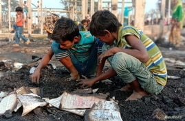 Children look at debris after a fire outbreak in Rohingya refugee camp, in Cox's Bazar, Bangladesh, Jan. 14, 2021.