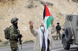 A demonstrator holding a Palestinian flag gestures as he stands next to Israeli forces during a protest against Israeli…
