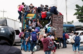 Hondurans climb onto the back of a truck for a ride in a new caravan of migrants, set to head to the United States, in Cofradia…