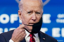 U.S. President-elect Joe Biden adjusts his face mask as he speaks about his plan to administer coronavirus disease (COVID-19)…