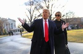 U.S. President Donald Trump gestures as he and first lady Melania Trump depart the White House to board Marine One.