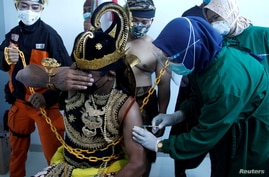 An Indonesian healthcare worker injects a dose of Sinovac's vaccine to a man dressed in Indonesia's traditional human puppet…