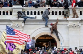 FILE PHOTO: A mob of supporters of U.S. President Donald Trump fight with members of law enforcement at a door they broke open…