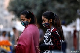 Women with masks against COVID-19 walk outside a market in Karachi, Pakistan, Jan. 25, 2021.