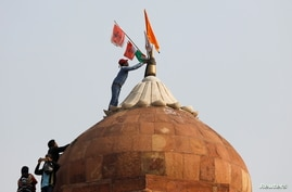A man holds a flag as he stands on the top of the historic Red Fort during a protest against farm laws.