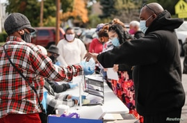 Volunteer hands out masks for coronavirus disease (COVID-19) survival kits as part of an outreach program to the Black community to increase vaccine trial participation in Rochester, New York.