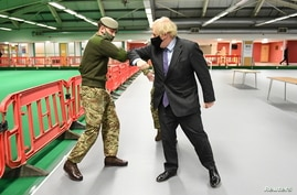 British Prime Minister Boris Johnson meets troops as they set up a vaccination center in the Castlemilk district of Glasgow.