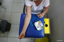 FILE PHOTO: Reuters senior correspondent Aislinn Laing prepares to give a blood sample at a medical facility before receiving a…