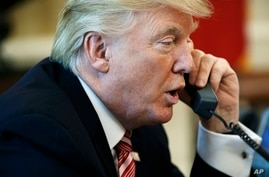 FILE - In this June 27, 2017, photo, President Donald Trump talks on the telephone in the Oval Office of the White House.