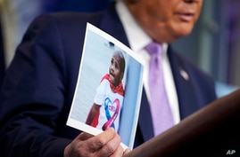 President Donald Trump holds a photo of LeGend Taliferro as he speaks at a news conference in the James Brady Press Briefing…