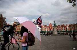 A tour operator stands under an umbrella with a British and American flag as she waits for customers in the center of Bruges, Belgium, Sept. 2, 2020.
