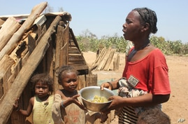 Toharano, mother of 18 children, with two of her children, holds a bowl in the village of Ankilimarovahatsy, Madagascar, Nov. 9, 2020.