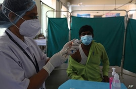 A health worker participates in a COVID-19 vaccine delivery system trial in Hyderabad, India, Saturday, Jan. 2, 2021. India…