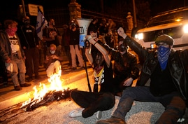 Israeli protesters chant slogans and block a road during a demonstration against Israeli Prime Minister Benjamin Netanyahu near…
