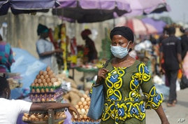 A woman wearing a face mask to protect against coronavirus, walks on a street, in Lagos, Nigeria , Thursday, Dec. 31, 2020. A…
