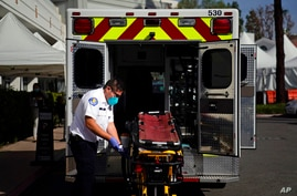 An EMT disinfects a gurney after transporting a patient at St. Joseph Hospital in Orange, Calif., Thursday, Jan. 7, 2021…