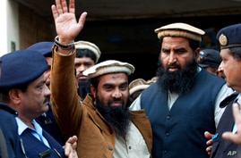 FILE - In this Thursday, Jan. 1, 2015, file photo, police officers escort Zaki-ur-Rehman Lakhvi, center, the main suspect of…