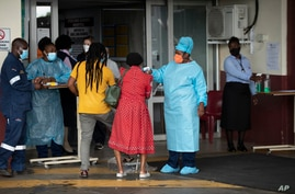 A health worker checks the temperature of an elderly patient at the emergency entrance of the Steve Biko Academic Hospital in…
