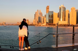Tourists look at the skyline at sunset, in Dubai, United Arab Emirates, Tuesday, Jan. 12, 2021. Since becoming one of the world…
