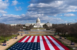 A large American Flag is are placed on the National Mall, with the U.S. Capitol behind, ahead of the inauguration of President…