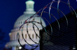 In this Jan. 19, 2021 photo, riot fencing and razor wire reinforce the security zone on Capitol Hill in Washington.  The…