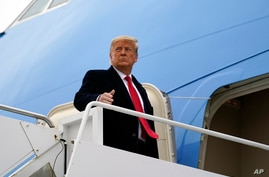 FILE - President Donald Trump gestures as he boards Air Force One upon arrival at Valley International Airport, in Harlingen, Texas, Jan. 12, 2021.