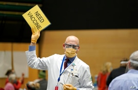 "Dr. John Corman, the chief clinical officer for Virginia Mason Franciscan Health, holds a sign that reads ""Need Vaccine"" to…"