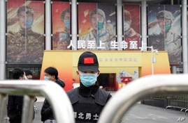 A security officer wearing a mask and a cap with the Chinese national flag guards the entrance after the World Health…