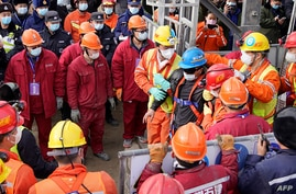 One (C-blue helmet) of twenty-two Chinese miners is rescued from hundreds of meters underground where they had been trapped for two weeks after a gold mine explosion in Qixia, in eastern China's Shandong province, Jan. 24, 2021.