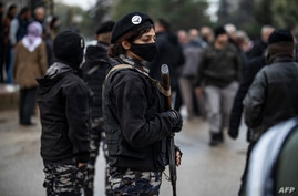 FILE - Members of Kurdish security forces known as Asayish stand guard in the northeastern Syrian city of Qamishli, Jan. 20, 2021.