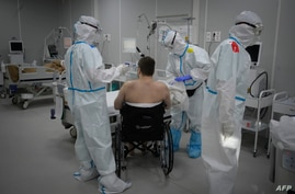 FILE - Medical workers in protective suits treat a patient (not the author of this story) infected with the coronavirus, at a makeshift hospital set up at the Sokolniki Exhibition and Convention Center in Moscow, Russia, Nov. 9, 2020.