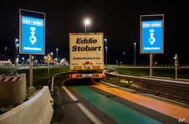FILE - A truck from Britain drives through a customs area to enter France at the Eurotunnel terminal, in Coquelles, northern France, Jan. 1, 2021.