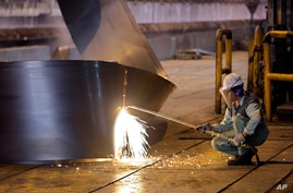FILE - A worker cuts a steel roll at the Mobarakeh Steel Complex, some 460 kilometers south of Iran's capital Tehran, May 31, 2012.