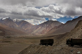 FILE - Indian army trucks drive near Pangong Tso lake near the India-China border, Sept. 14, 2017, in India's Ladakh region, where the two countries continue to be locked in a standoff.