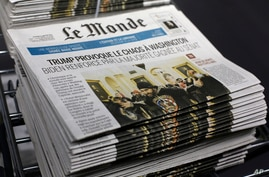 """Copies of the French newspaper Le Monde with the headline """"Trump Provokes Chaos in Washington"""" are seen at at Le Monde headquarters, in Paris, Jan. 7, 2021."""
