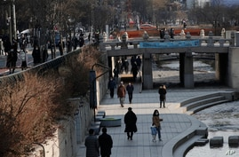 People wearing face masks walk during a lunch break at Cheonggye stream in downtown Seoul, South Korea, Jan. 4, 2021.