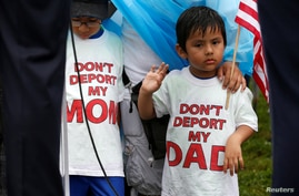 FILE - Boys wearing T-shirts calling for their parents not to be deported stand during a rally by immigration activists in Washington, D.C., Aug. 15, 2017.