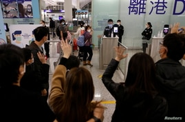 FILE - Members of a family, who are emigrating to Scotland, wave good-bye to their friends who are seeing them off before their departure at Hong Kong International Airport in Hong Kong, Dec. 17, 2020.