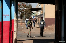 FILE - A soldier patrols the streets ahead of planned anti-government protests amid the coronavirus pandemic, in Harare, Zimbabwe, July 30, 2020.