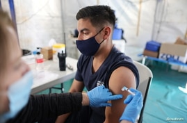 Orange County firefighter Christopher Huerta receives the COVID-19 vaccine in Irvine, California, Jan.27, 2021.